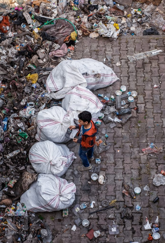 A man standing, surrounded by different types of garbage.