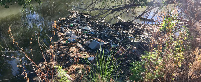 Plastic garbage thrown on a riverside.