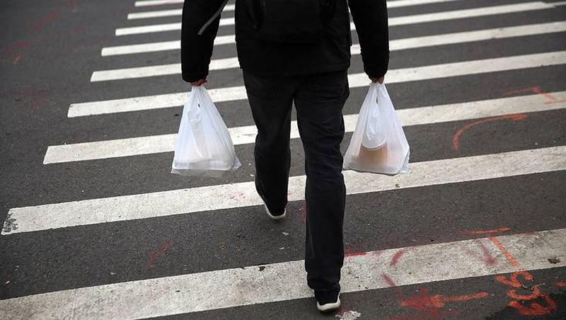 A man holding two plastic bags while crossing the street on a pedestrian lane.