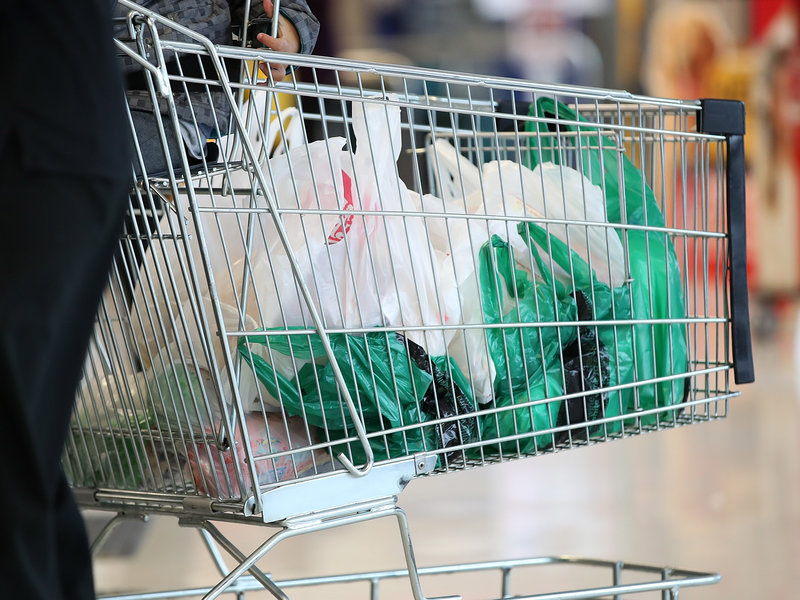 Plastic bags with items inside placed in a grocery cart.