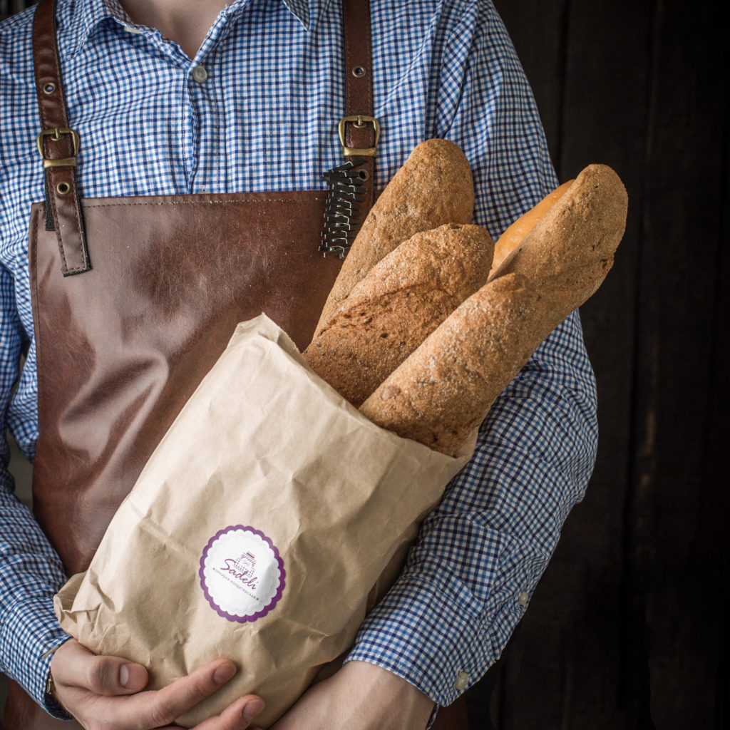 A man carrying a brown recyclable paper bag with toasted breads placed inside.